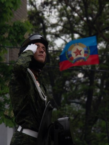 Soldat vor der Flagge der Volksrepublik Lugansk (LNR)
